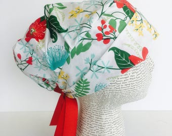 Ribbon Tie Back Surgical Scrub Cap scrub hat featuring a white material with flowers in red yellow blue and green with a matching red ribbon