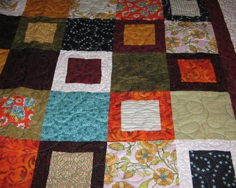 """Brilliant, Rich prints in this 85X91 Queen Size Quilt of 6"""" blocks in turquoise, tangerine, maroon, olive, and white."""