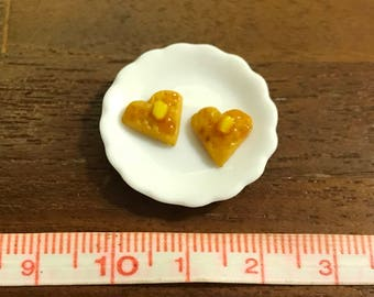 Two heart shaped waffles with maple syrup and butter