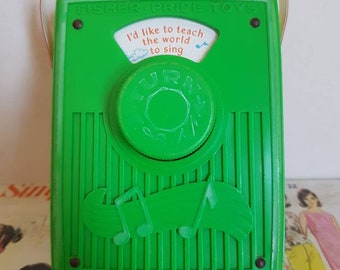 Vintage Fisher Price pocket Radio Id like to teach the world to sing kitsch graphics green wind up musical toy
