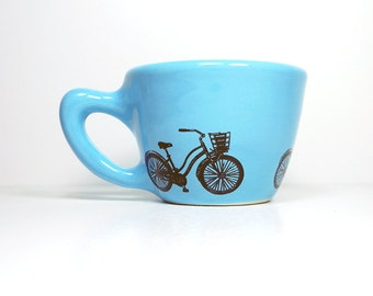 12oz cup featuring a speedy delivery bike print, shown here on cloudless blue glaze - Made to Order / Pick Your Colour