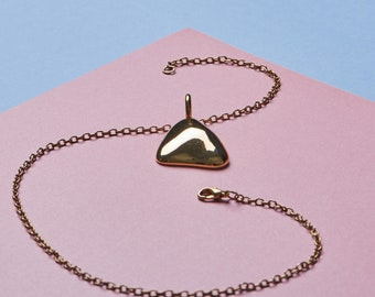 Geometric pendant on gold toned chain necklace