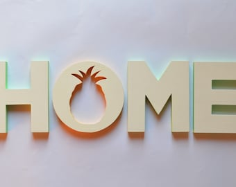 Writing HOME with wooden pineapple