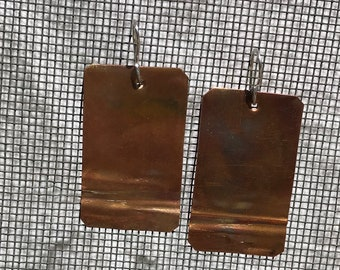Handmade copper earrings flame painted , textured by folding and heating .