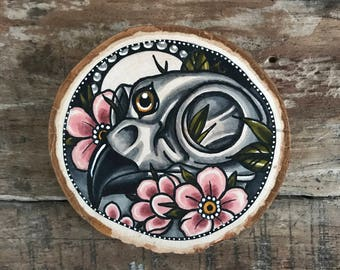 Wood slice with an original drawing of a bird skull