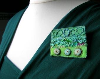 A unique hand crafted upcycled mixed media hand embroidered green and turquoise crazy patchwork brooch