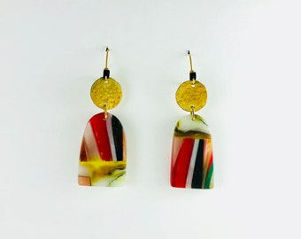 Swinging Sisters: handmade resin, strong contrasting color, red, blue, black, green and skin tone, combined with brass