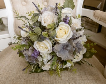 Rustic ivory and lavender wedding bridal bouquet. Made with artificial roses, hydrangea, heather, lavender and simple greenery.