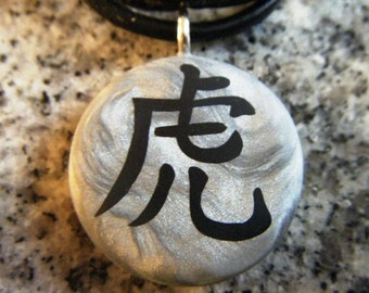 Chinese Zodiac signs TIGER hand carved on a polymer clay grey pearl color background. Pendant comes with a FREE necklace