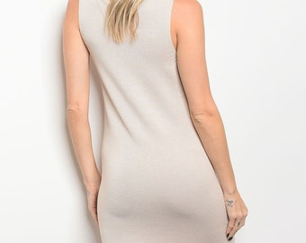 Ladies fashionsleeveless chunky knit sweater dress that features a rounded neckline and fringe trim