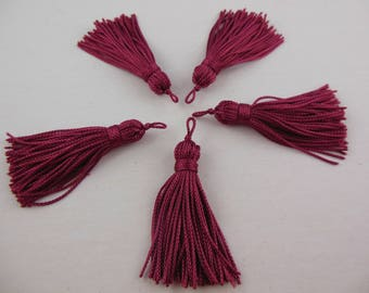 A cranberry color rayon thread tassel
