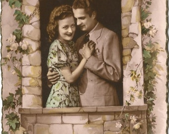 Romantic French Couple posing in Garden Wall with Ivy and Roses surrounding the opening Pastel Pink Hue Vintage Postcard