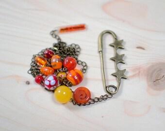 Sautoir épingle étoilée en métal façon bronze vieilli et perles en verre fantaisie couleur jaune, orange et rouge - verre - métal