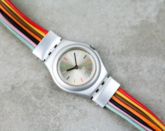 Vintage womens Swatch watch with silver sunburst dial and colorful cable band