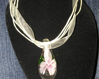 Pink glass flower pendant on a white ribbon cord necklace