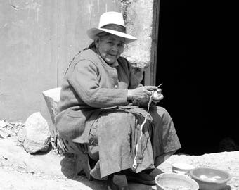 Peruvian woman peeling potatoes in front of her house.