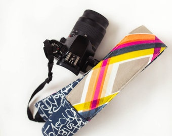 DSLR camera strap cover with lens cap pocket.  bright plaid with words.