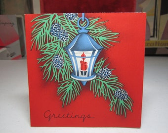 Vintage art deco 1930's-40's christmas card bright red with a blue lantern with tree branches and pine cones