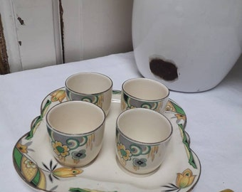 Pretty and practical art deco ceramic egg cup and plate set. Yellow, grey and green colour palette on cream ground