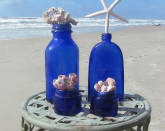 Set of Four Vintage Antique Blue Bottles with Starfish, Coral and Barnacles
