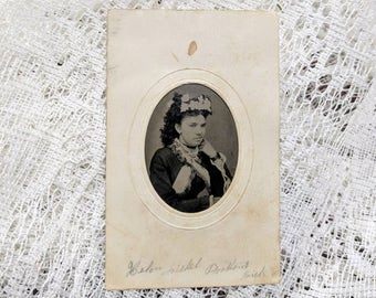 Identified Tintype photograph of a beautiful fashionably dressed woman in a paper frame wearing a smirk