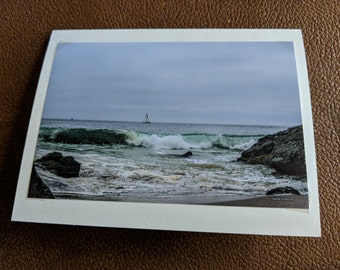 Sailboat on the ocean with waves crashing on the shore
