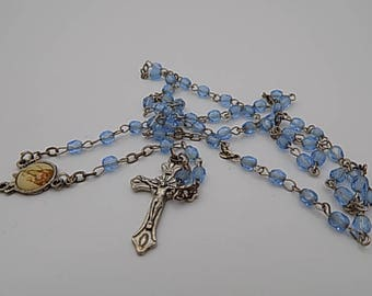 Rosary, religious relic cross statue statue in silver glass beads, on the cross and glass beads