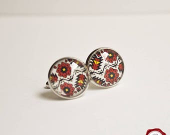 Glass cuff links with floral folk pattern in black and red on white background