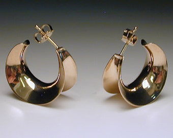 A classic little 14K Solid Gold Shiny Anticlastic hoop earring with a lot of drama.