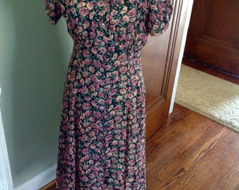 Vintage dress with pink roses...black background...front buttons....fitted at the waist.