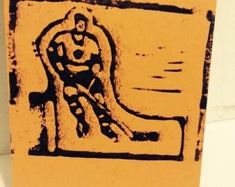 Handmade linocut orange note card with toy rod hockey guy