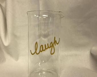 """Glass beaker with the word """"laugh"""""""