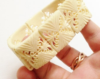 Bracelet - elasticated pieces pierced highly ornate  carved cream plastic bangle