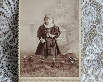 Beautiful Victorian little girl holding flowers with long hair and bangs