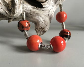 Unique necklace of 5 hand-blown hollow beads made from Murano glass. Beads are coral color with varied patterns of black.