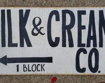 Hand painted, black and white Milk & Cream Co. sign on reclaimed wood.