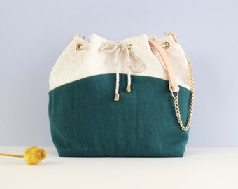 Gisèle: bucket bag made of and off-white cotton, green linen, lurex piping and golden chain.