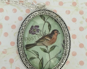 Silvercoloured metal pendant featuring bird on a green background