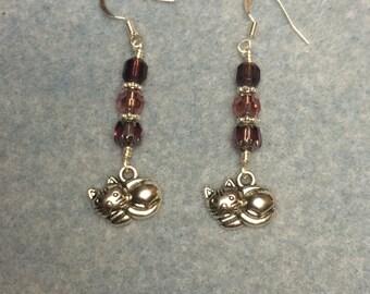 Silver sleeping cat charm dangle earrings adorned with purple Czech glass beads.