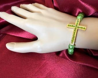 Gold colored cross with green rhinestones and round green beads stretchy bracelet
