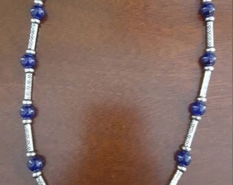 Blue glass beads and long silver spacers with a silver lobster claw clasp.