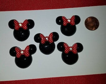 Minne Mouse like with black with a red white Polk a dot bow and rhinestone in the middle. Embellishments, scrapbooking, hair bow, crafts.