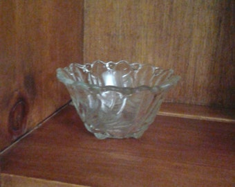 Small clear glass bowl with flower design in bottom and leaves up sides