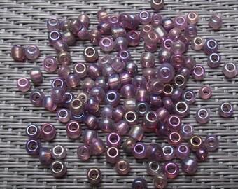 500 on average 3 mm iridescent purple glass seed beads.