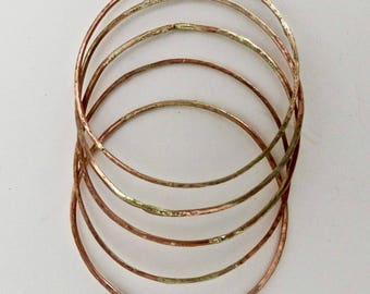 Five copper and silver staking bracelets.