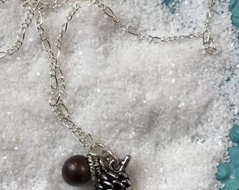 Sterling silver figaro chain with mounted pearl and pinecone charm