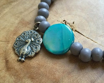 Blue Peacock: an elastic beaded bracelet with grey wooden beads, turquoise mother of pearl and a metal charm in the shape of a peacock