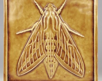 "Sphinx Moth Tile 7 1/2"" sq. x 1/2""  transparent nickel glaze high fired stoneware."