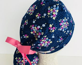 Ponytail Scrub Cap scrub hat featuring a dark blue material with flowers in blue purple and yellow with a matching pink ribbon