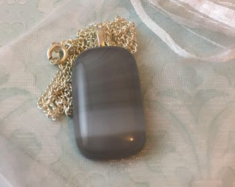 Gorgeous understated grey fused glass pendant style necklace.